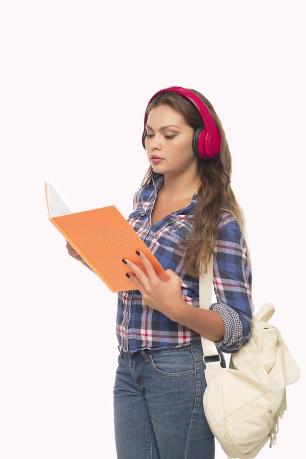 Älskvärd studentflicka som lyssnar till musik arkivbilder