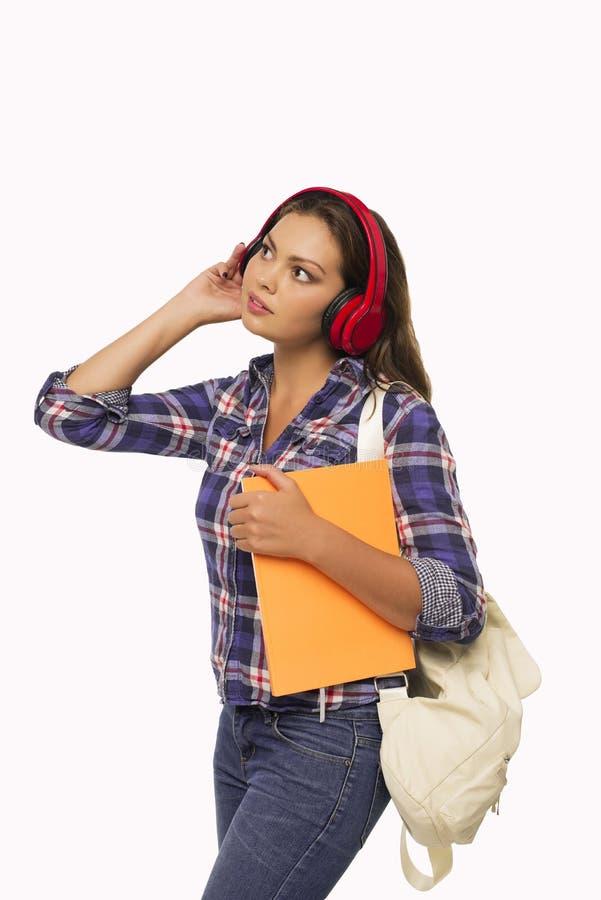 Älskvärd studentflicka som lyssnar till musik royaltyfria bilder