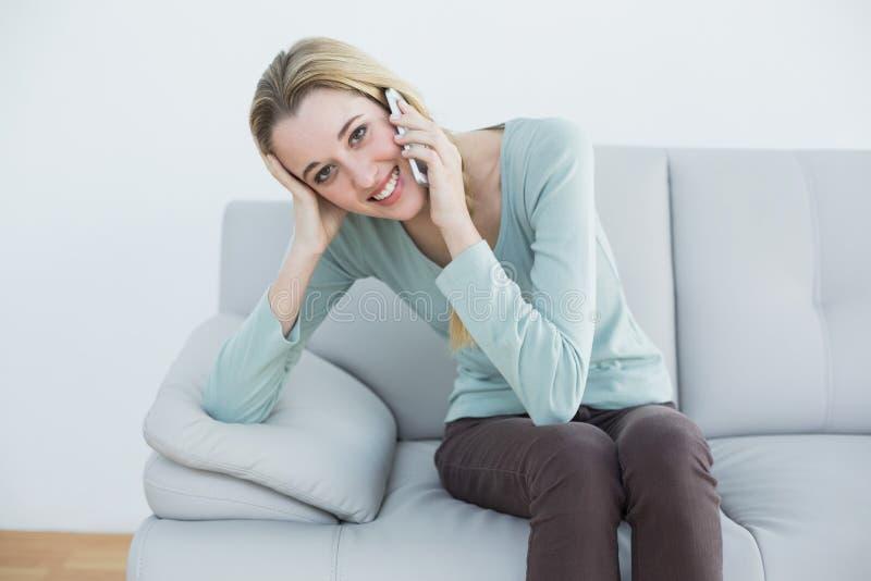 Älskvärd tillfällig kvinna som ringer, medan sitta på soffan royaltyfria foton