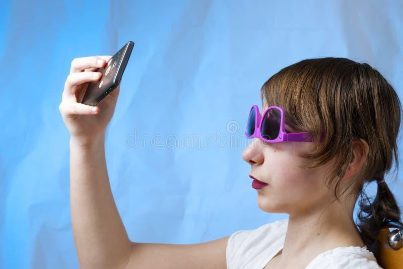 Älskvärd trevlig uppdiktad flicka med telefonen royaltyfri fotografi