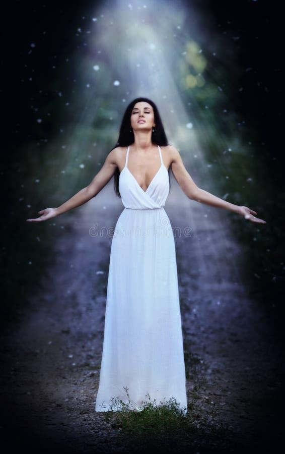 Älskvärd ung dam som bär en elegant lång vit klänning som tycker om strålarna av himmelskt ljus på hennes framsida i förtrollade  arkivfoton