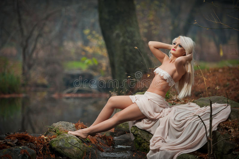 Älskvärd ung dam som sitter nära floden i förtrollade trän Den sinnliga blondinen med vit beklär att posera provocatively i höstl fotografering för bildbyråer