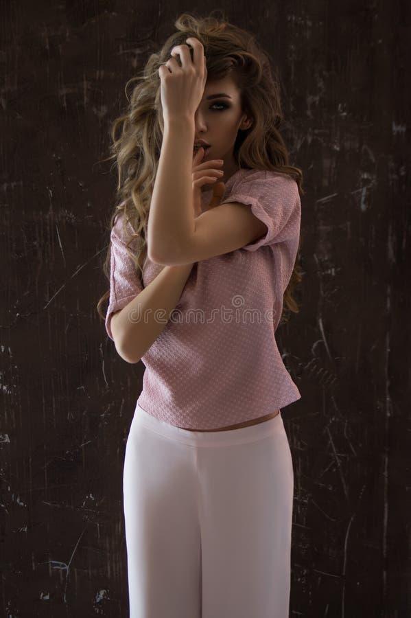 Älskvärd ung flicka med långt lockigt hår arkivfoto