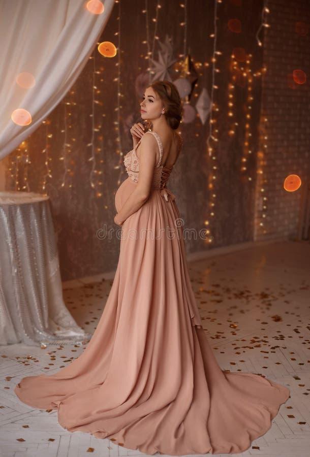 Älskvärd ung gravid kvinna i en härlig klänning royaltyfri foto