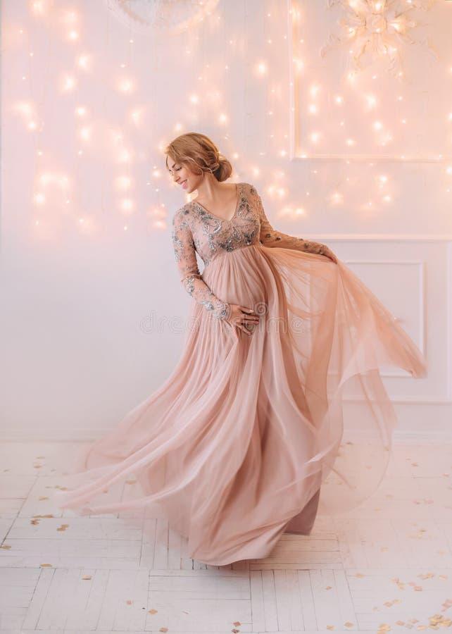 Älskvärd ung gravid kvinna i en härlig klänning arkivbild