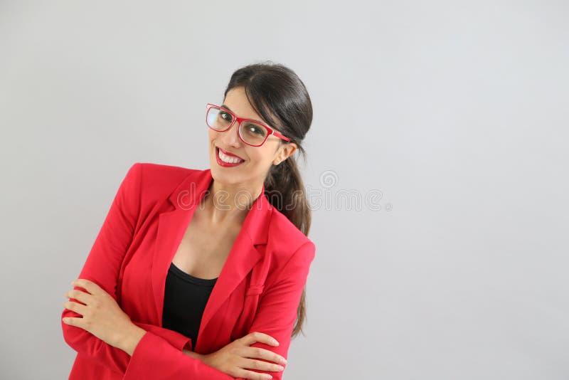 Älskvärd ung kvinna med det isolerade röda omslaget arkivfoto