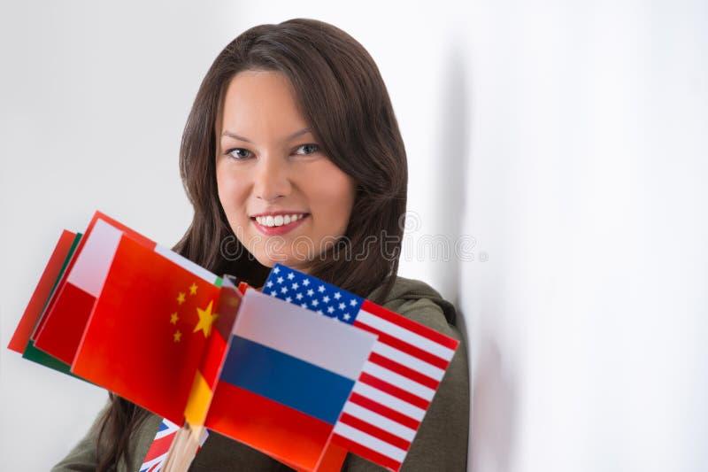 älskvärd ung kvinna med olika flaggor fotografering för bildbyråer
