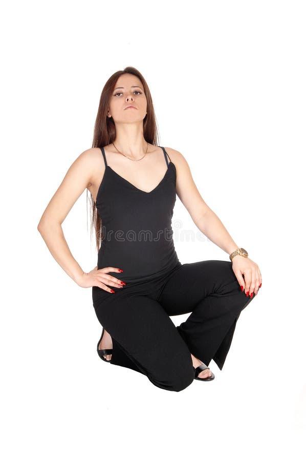 Älskvärd ung kvinna som huka sig ned på golvet i svart dräkt arkivbild