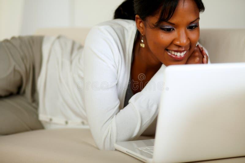 Älskvärd ung kvinna som ler och ser till bärbar dator royaltyfria foton