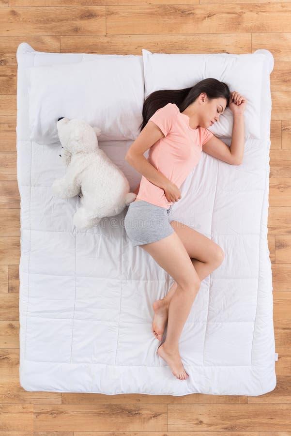 Älskvärd ung kvinna som sover på säng royaltyfri fotografi