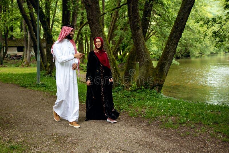 Älskvärda arabiska par i traditionell kläder som utomhus omfamnar royaltyfri bild