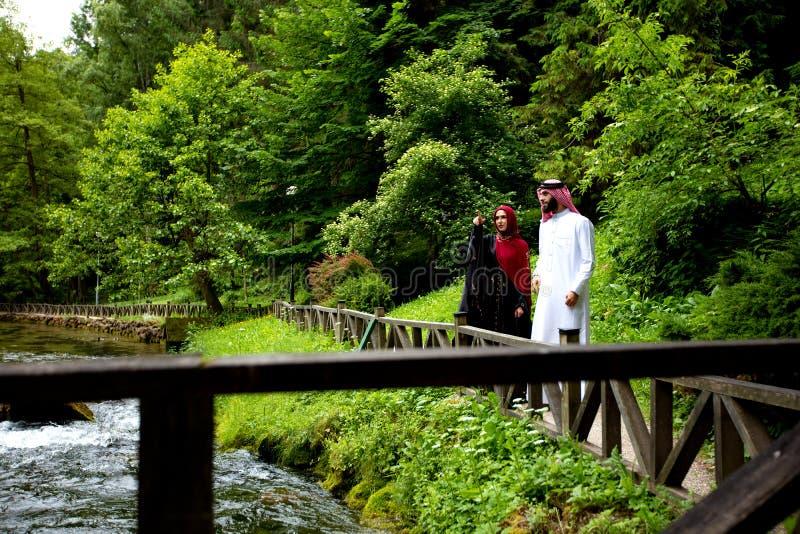 Älskvärda arabiska par i traditionell kläder som utomhus omfamnar arkivbilder