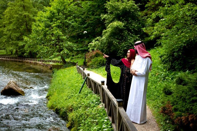 Älskvärda arabiska par i traditionell kläder som utomhus omfamnar royaltyfri fotografi
