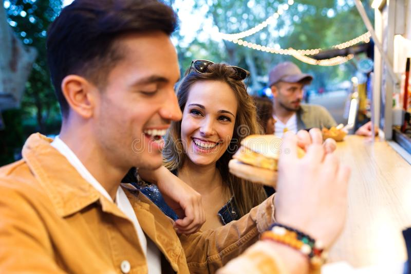 Älskvärda attraktiva par som tillsammans delar och äter hamburgare I fotografering för bildbyråer