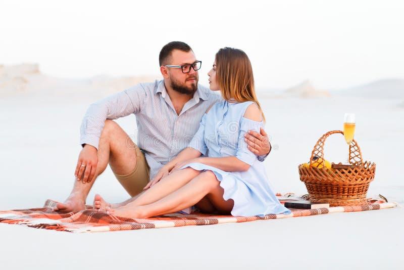 Älskvärda attraktiva par som tillsammans sitter på den vita sandstranden, lyckliga par som tycker om picknicken på stranden och,  arkivbild