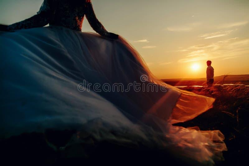 Älskvärda brölloppar i solnedgång Brud som kör till hennes brudgum Man på bsckgrounden arkivfoto