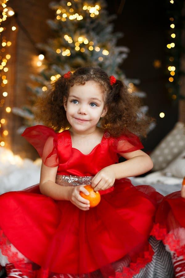 Älskvärda flickor med lockigt hår i röda klänningar med tangerin i handen som sitter på säng i jul, dekorerade rum med granträdet royaltyfri fotografi