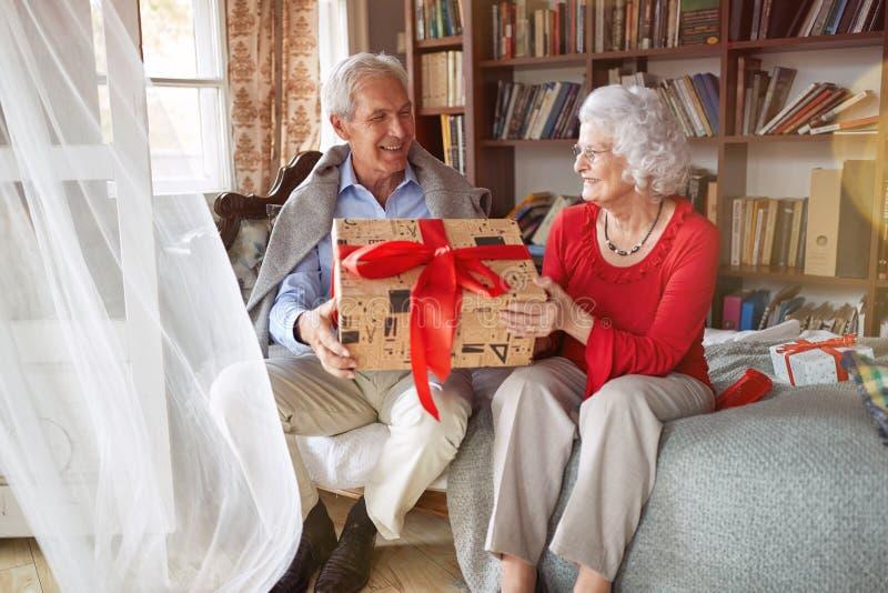 Älskvärda höga par som utbyter julgåvor arkivbilder