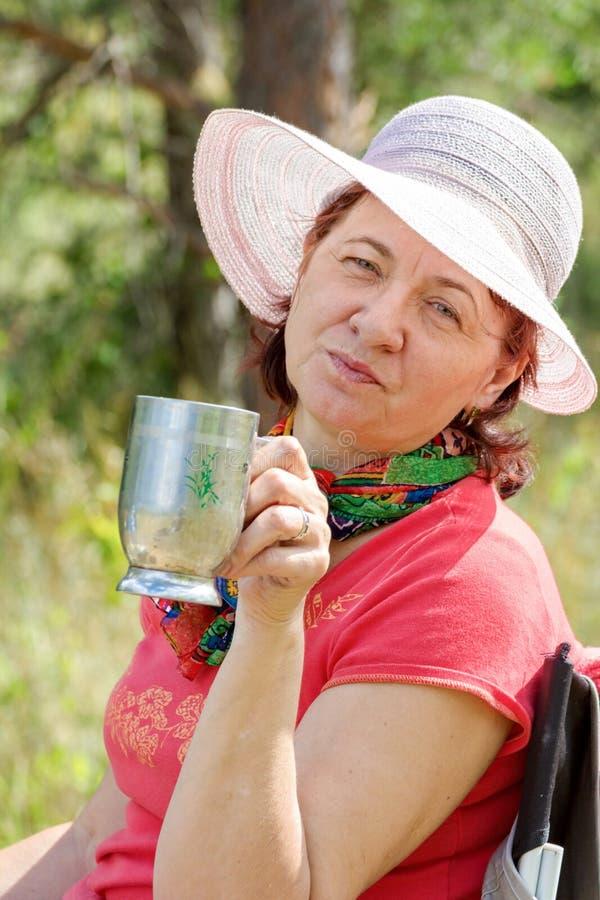 Älskvärda mogna brunettcts i en vardagsrumstol som dricker kaffe på en sommardag arkivfoton