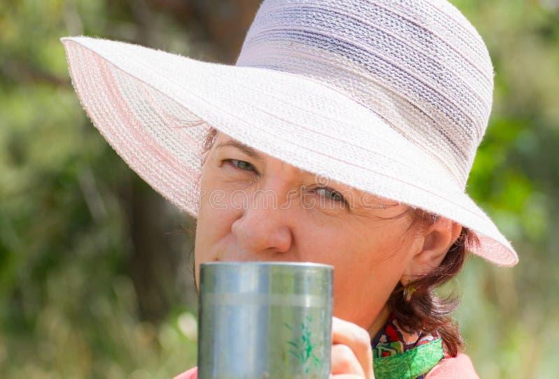 Älskvärda mogna brunettcts i en vardagsrumstol som dricker kaffe på en sommardag arkivfoto