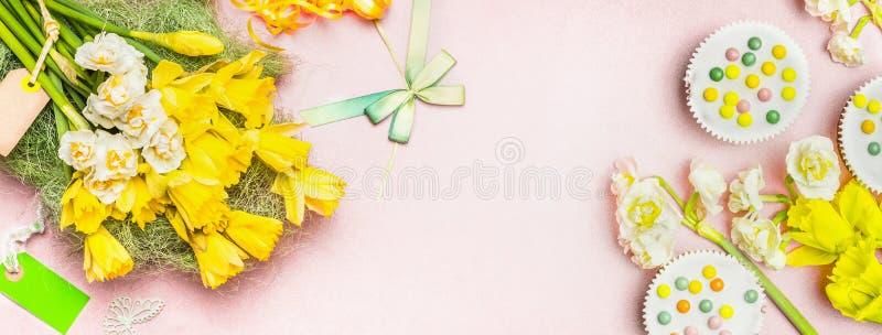 Älskvärda påskliljablommor, tom etikett, kaka och garneringar på blek bakgrund för pastellfärgade rosa färger, bästa sikt, baner royaltyfria foton