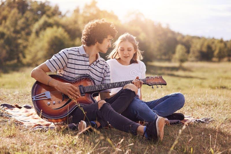 Älskvärda par av tonåringar spenderar fri tid tillsammans, har datumet, tycker om utomhus- fridsam atmosfär i äng Den romantiska  fotografering för bildbyråer