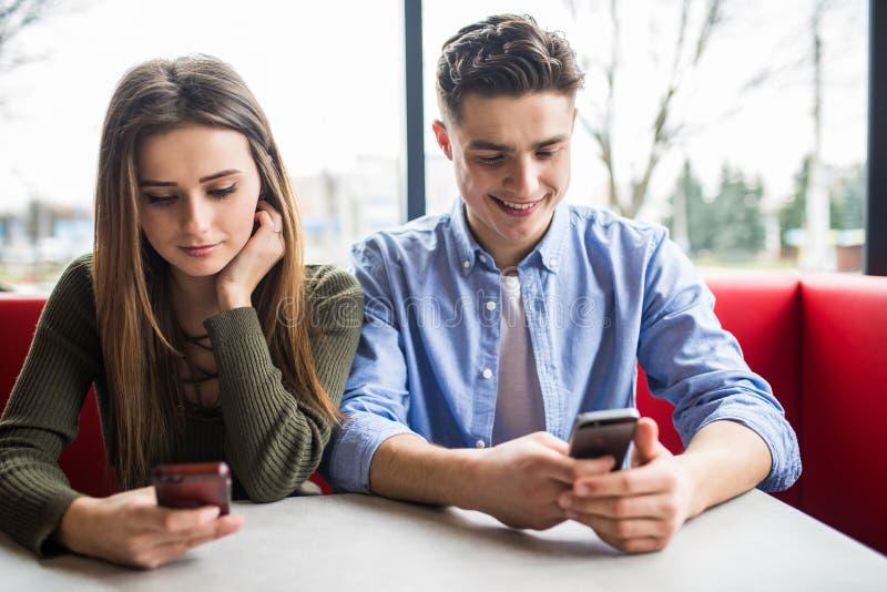 Älskvärda par genom att använda smarta telefoner som ser mobilt le Telefonknarkare royaltyfri foto