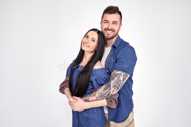 Älskvärda par har den varma omfamningen, poserar för familjståenden, leende joyfully, har bra förhållanden Den tillgivna brodern  royaltyfria bilder