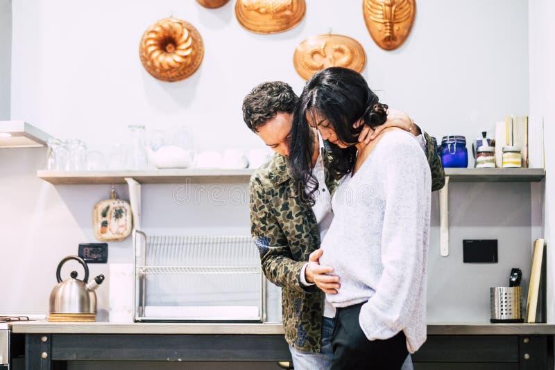 Älskvärda par henne som är gravid i köket hemma som trycker på buken och att bo med glädje som väntan av det nytt behandla som et royaltyfri fotografi
