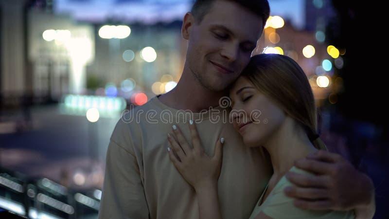 Älskvärda par som kramar ömt mot nattstadsbakgrund, romantiskt datum arkivbilder
