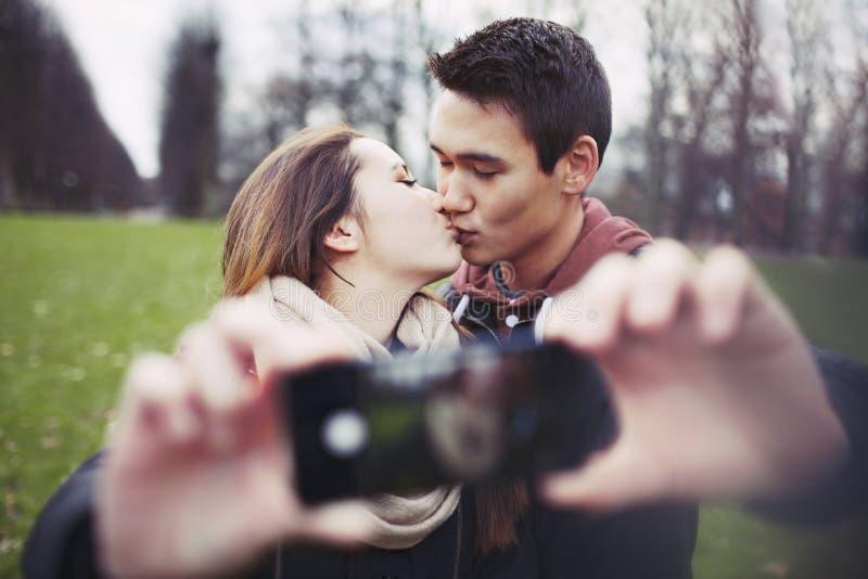 Älskvärda par som tar självståenden, medan kyssa royaltyfria foton