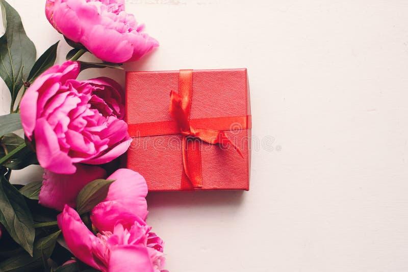 Älskvärda rosa pioner med den röda gåvaasken på lantlig vit träbac royaltyfri bild