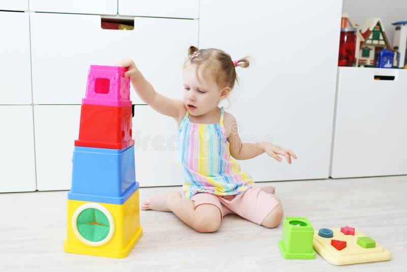 Älskvärda små 2 år litet barnflicka som spelar med den bildande leksaken arkivfoto