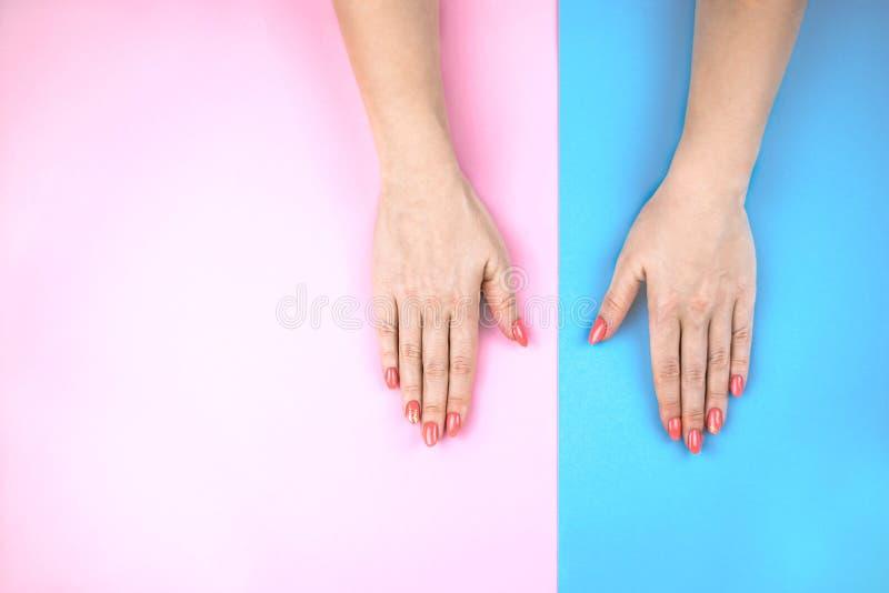 Älskvärda ung kvinnas händer på kulör bakgrund royaltyfria foton