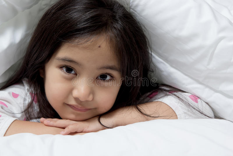 Älskvärt asiatiskt barn som lägger ner på sängen fotografering för bildbyråer