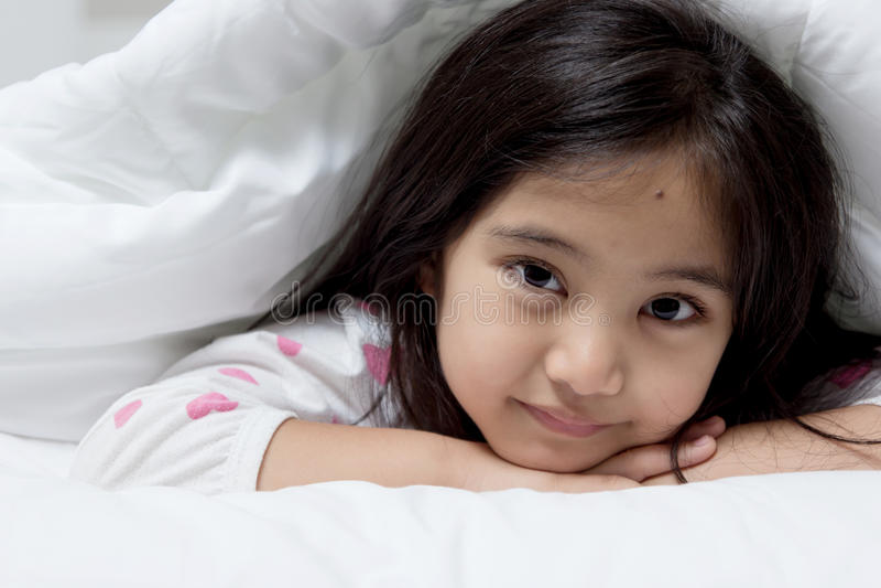 Älskvärt asiatiskt barn som lägger ner på sängen royaltyfri bild
