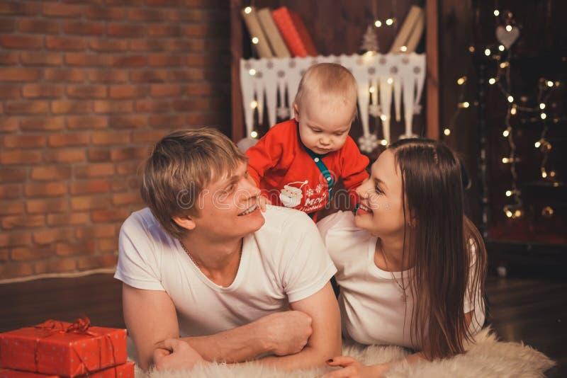 Älskvärt behandla som ett barn pojken i den Santa Claus dräkten för jul Moder fa royaltyfri fotografi