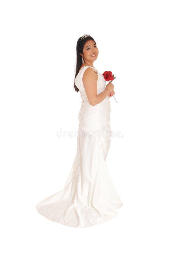 Älskvärt brudanseende i en vit kappa med den röda rosen fotografering för bildbyråer