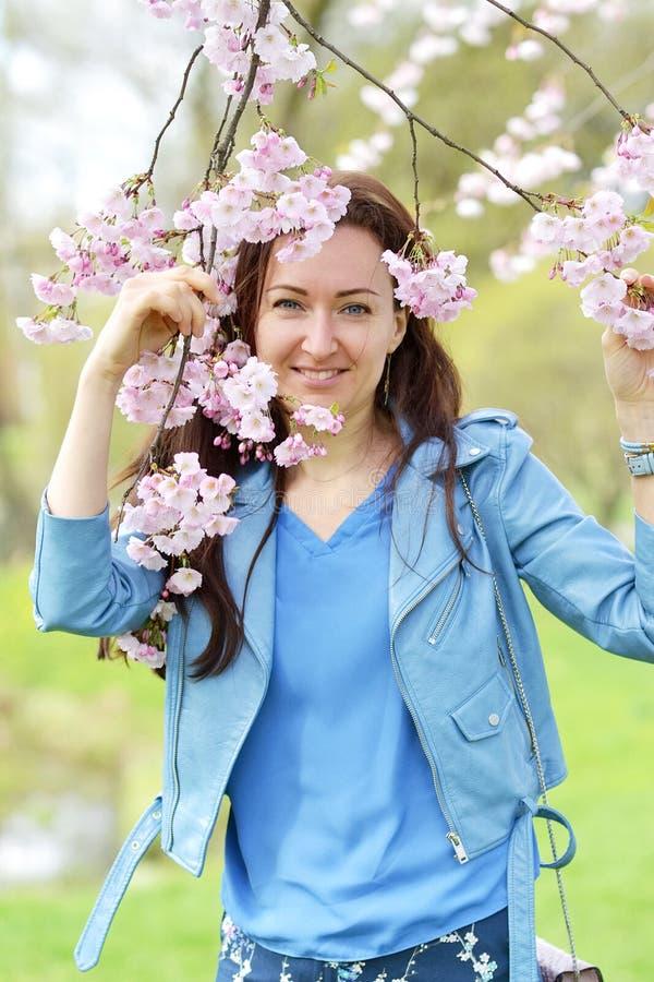 Älskvärt härligt Caucasian kvinnaanseende som poserar på bakgrunden av att blomma den Japan körsbäret royaltyfria foton