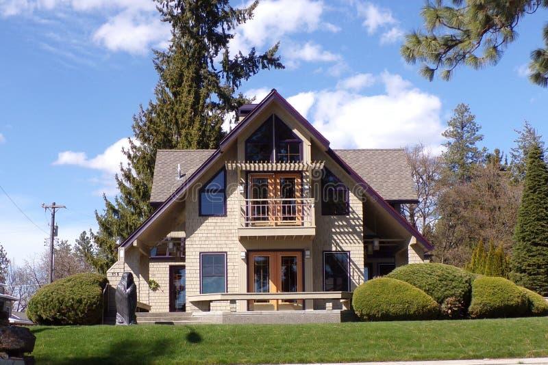 Älskvärt hem med lilaklippning och frodigt landskap arkivfoto
