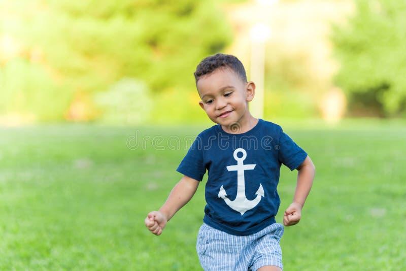 Älskvärt pojkespela och spring i parkerar utomhus arkivbild