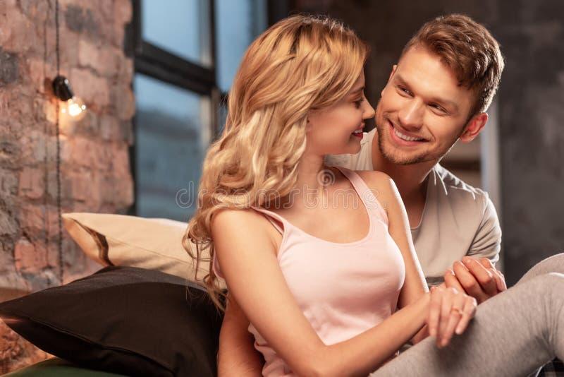Älskvärt rättvist gift par som tillsammans tycker om tid i sovrummet fotografering för bildbyråer