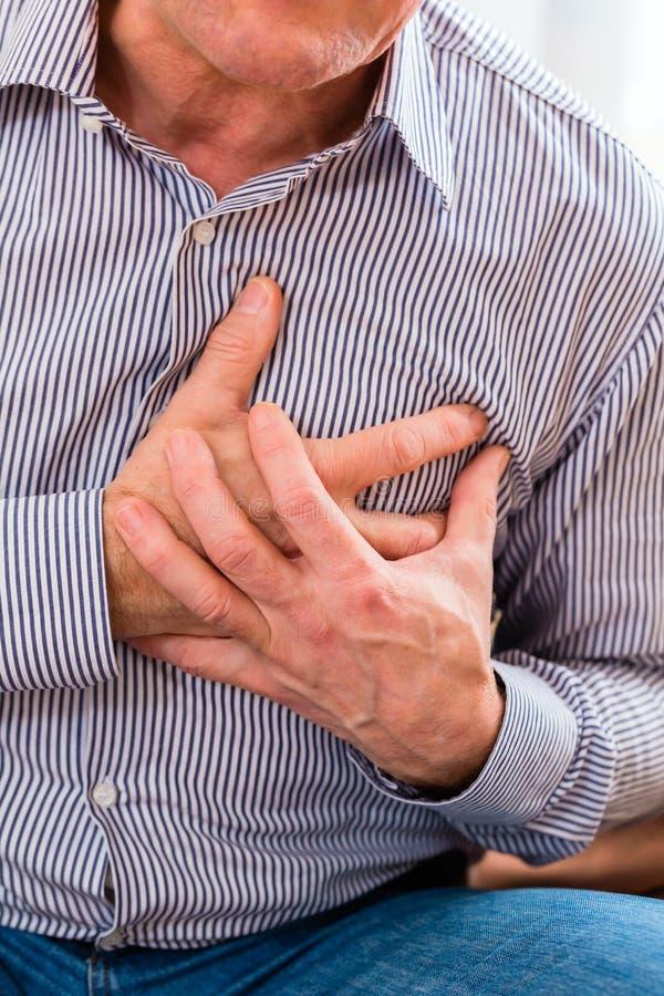 Älter, Herzinfarkt habend zu Hause stockfotografie