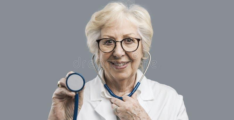 Ältere Ärztin, die ein Stethoskop verwendet stockfoto