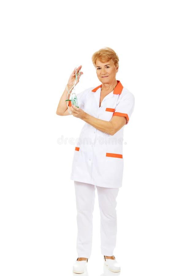 Ältere Ärztin oder Krankenschwester des Lächelns hält Sauerstoffmaske stockbilder
