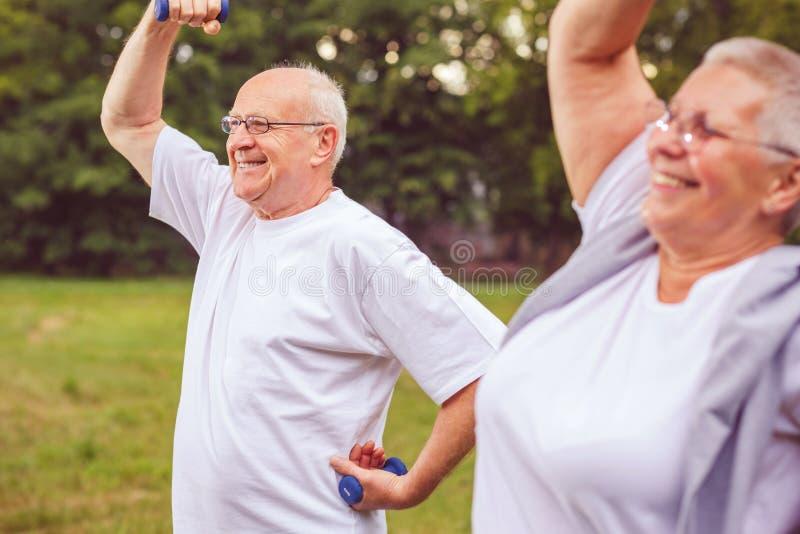 Ältere Übung - älterer Mann und Frau sind draußen in einer Parkübung mit Dummköpfen und Habenspaß zusammen stockbilder