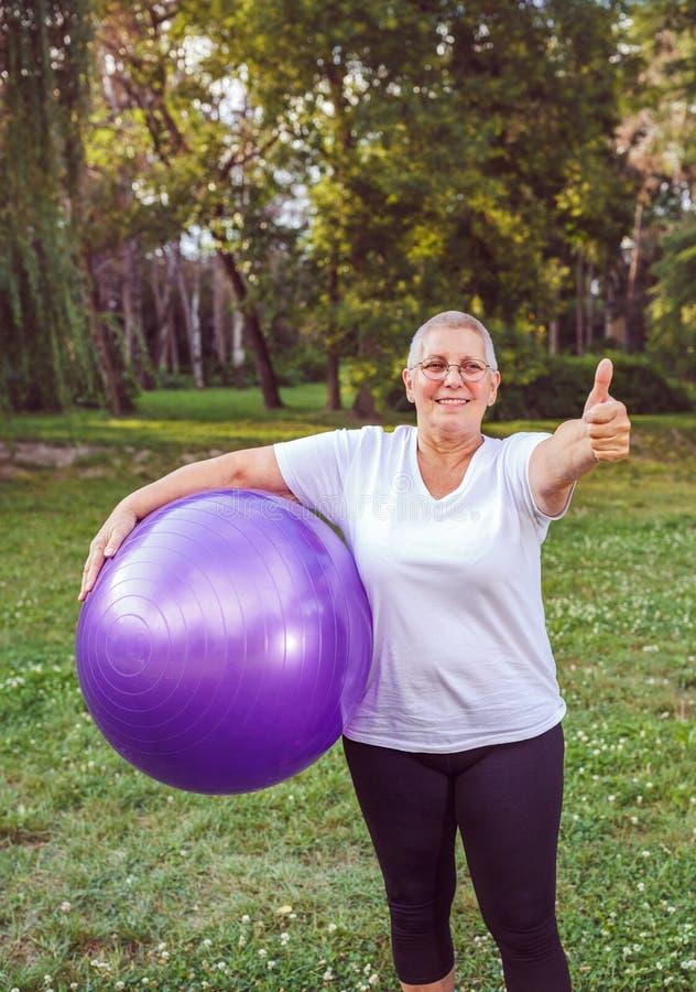 Ältere Übung - Daumen oben für gesunde trainierende Frau mit Eignungsbällen im Park lizenzfreie stockbilder