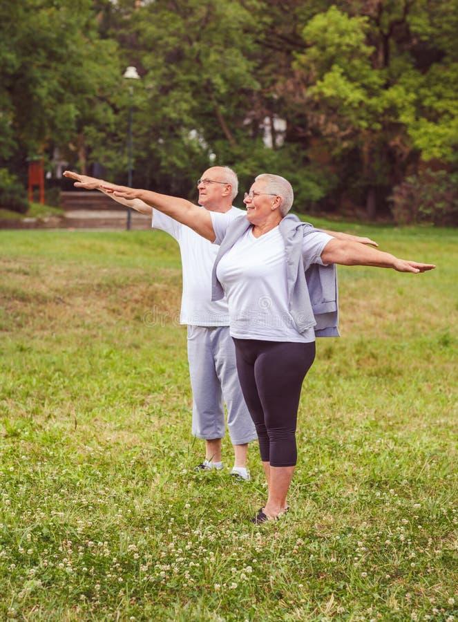 Ältere Übung - gesundes gealtertes Paar, das zusammen nach Sportübungen uns Training besser stillsteht stockbild