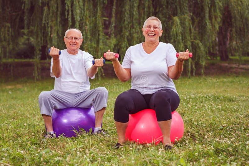 Ältere Übung - Pensionärpaar, das Dummköpfe beim Sitzen auf Eignungsball im Park hält stockfotos