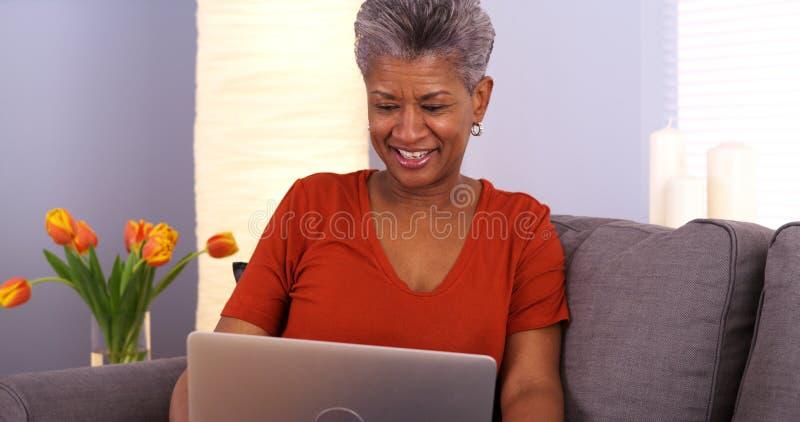 Ältere Afrikanerin, die Spaß mit Laptop hat lizenzfreie stockfotos